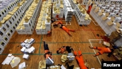 Workers lay during a break as they prepare election materials before their distribution to polling stations in a warehouse in Jakarta, Indonesia, April 15, 2019. (REUTERS/Willy Kurniawan)