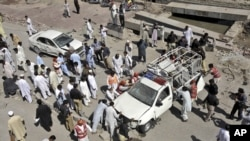 Pakistani police, rescue workers and civilians push back a police vehicle which was hit by roadside bomb, in Peshawar, Pakistan, May 12, 2012.
