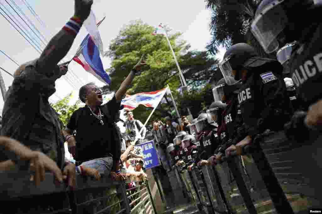 Anti-government protesters gesture towards riot police outside the headquarters of the ruling Puea Thai Party of Prime Minister Yingluck Shinawatra in Bangkok, Nov. 29, 2013.
