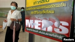 A woman wearing a mask walks past an information banner on Middle East Respiratory Syndrome (MERS) at the entrance of Bamrasnaradura Infectious Diseases Institute on the outskirts of Bangkok, Thailand, June 19, 2015.