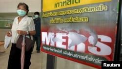 Žena na Tajlandu sa maskom pored postera koji upozorava na MERS