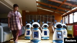 A staff walks past robots serving at a nursery home in Hangzhou, Zhejiang Province, China, May 17, 2016.