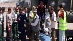 資料照:阿富汗和中國官員在喀布爾從直升機上運下裝有在昆都士被殺害的中國修路工人的屍袋。 (2004年6月11日)