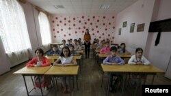 格鲁吉亚一名老师和她的5年级的学生2015年6月8日在首都第比利斯的一所公立小学里。