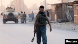 An Afghan policeman arrives at the site of an attack in Jalalabad city, Aug. 30, 2014.