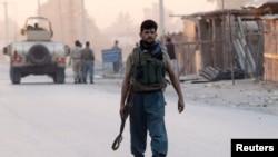 Seorang polisi Afghanistan tiba di lokasi serangan di kota Jalalabad (30/8).