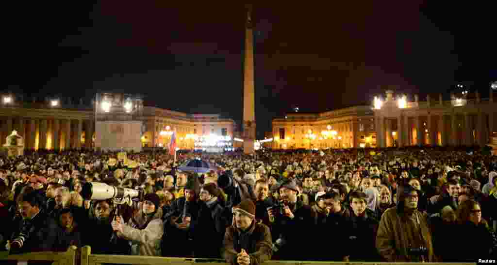 People crowd Saint Peter's Square to await the sight of smoke from the chimney above the Sistine Chapel, March 12, 2013.