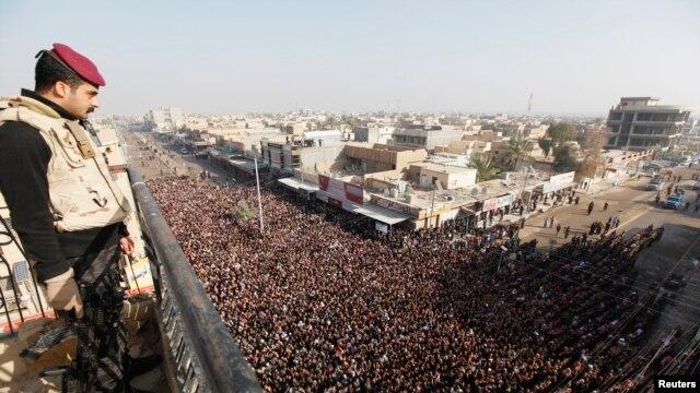 Seorang polisi Irak tengah mengawasi jalannya prosesi pemakaman korban bentrokan antara petugas keamanan dan warga di n Falluja, 50 kilometer sebelah barat Baghdad, 26 January 2013. (REUTERS/Thaier Al-Sudani). Kelompok terkait al-Qaida di Irak menghimbau warga SUni untuk mengangkat senjata melawan pemerintah yang dipimpin golongan Syiah (1/2).