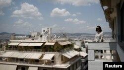 来自中国的29岁的潜在房产买家2018年5月25日在希腊雅典市中心的公寓的阳台向外张望。