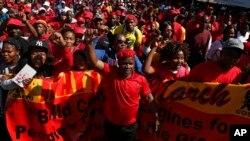 Des ouvriers marchent pour le 1er mai devant le bâtiment du Stock Exchange de Johannesburg, le 1er mai 2017.