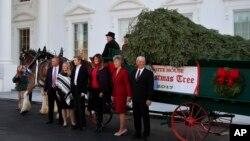 La primera dama de EE.UU., Melania Trump (3a. desde la derecha), su hijo Barron (3o. desde la izquierda), posan con la familia Chapman, propietarios de Silent Night Evergreens, una granja de pinos de Wisconsin, de donde proviene el abeto principal que se exhibirá en la Casa Blanca en la temporada navideña 2017.