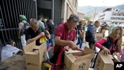 Empleados de un centro cultural de Venezuela apoyado por el gobierno en disputa de Nicolás Maduro reciben cajas con alimentos subsidiados distribuidos bajo el programa CLAP. Caracas, Venezuela, julio 6 de 2018. AP/Fernando Llano.