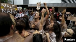FILE - Environmental activists chant slogans during a protest in front of the headquarters of Brazilian mining company Vale SA in downtown Rio de Janeiro, Nov. 16, 2015.