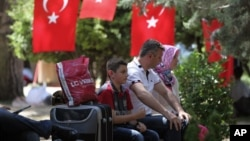 People rest in Kugulu Park in Ankara, Turkey, June 24, 2013. After weeks of sometimes-violent confrontation with police, Turkish protesters have found a new form of resistance: standing still and silent.