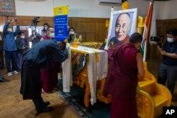 Presiden Administrasi Pusat Tibet Penpa Tsering, meletakkan syal upacara di depan potret pemimpin spiritualnya Dalai Lama dalam upacara untuk menandai ulang tahun ke-86 pemimpin Tibet di Dharmsala, India, Selasa, 6 Juli 2021. (AP)