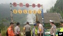 Polisi dan petugas penyelamat berdiri di jalan menuju Kawah Sileri di Dieng, Jawa Tengah pasca erupsi Minggu, 2 Juli 2017. Sebuah helikopter yang membawa delapan orang jatuh, Minggu (2/7) saat dalam perjalanan untuk membantu proses evakuasi. (AP Foto / Dwiana Jati Setiaji)