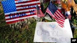 A memorial for U.S. Capitol Police officer Brian Sicknick is visible near the Capitol Building on Capitol Hill in Washington, Thursday, Jan. 14, 2021. Sicknick was killed by rioters in last Wednesday's attack on the Capitol Building. (AP Photo…