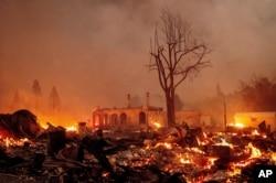 Buildings burn as the Dixie Fire tears through the Greenville community of Plumas County, California, Aug. 4, 2021.