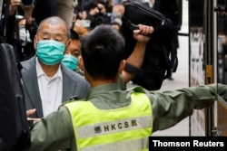 FILE - Democracy advocate Jimmy Lai, center, leaves the Hong Kong's Court of Final Appeal in Hong Kong, Feb. 9, 2021.