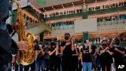 Waandamanaji wakiwa wamefunika nyuso zao wakikiuka katazo la hivi karibuni la kufunika nyuso jengo kubwa lenye maduka ya biashara Hong Kong, Oct.13, 2019.