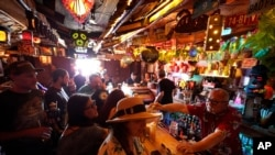 FILE - Patrons enjoy cold tropical cocktails in the tiny interior of the Tiki-Ti bar as it reopens on Sunset Boulevard in Los Angeles.