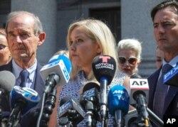 Virginia Giuffre, au centre, qui affirme avoir été victime de la traite des êtres humains par le délinquant sexuel Jeffrey Epstein, lors d'une conférence de presse devant un tribunal de Manhattan, à New York, le 27 août 2019.