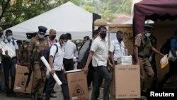 Polisi dan pejabat pemilihan Sri Lanka mengenakan masker saat mengangkut kotak suara dan kartu suara ke dalam bus dari pusat distribusi ke tempat pemungutan suara sebelum pemilihan parlemen negara yang dijadwalkan pada 5 Agustus, di Kolombo, Sri Lanka, 4 Agustus 2020.