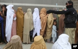 Women wait to receive cash under the government Ehsaas Emergency Cash Programme for families in need, during a government-imposed nationwide lockdown to help contain the spread of the coronavirus, in Peshawar, Pakistan, Monday, April 13, 2020