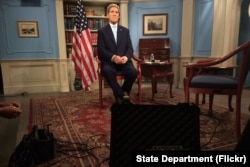 """U.S. Secretary of State John Kerry settles into his chair in a studio at the Department of State in Washington, D.C., before appearing on the MSNBC program """"Morning Joe"""" on July 17, 2015, to discuss the E.U./P5+1/U.S.-Iranian nuclear deal."""