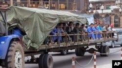 Des travailleurs chinois transportés sur une remorque en pleine rue de Kinshasa, RDC, 20 mai 2015.