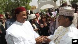 Mahamadou Issoufou, a hagu, da Seini Oumarou a dama suna gaisawa