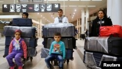 FILE - The al-Qassab family, Iraqi Christian refugees from Mosul, walk through the Beirut international airport ahead of their travel to the United States, in Beirut, Lebanon, Feb. 8, 2017.