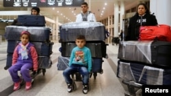 FILE - The al-Qassab family, Iraqi Christian refugees from Mosul, at Beirut international airport ahead of their travel to the United States, Lebanon, Feb. 8, 2017.