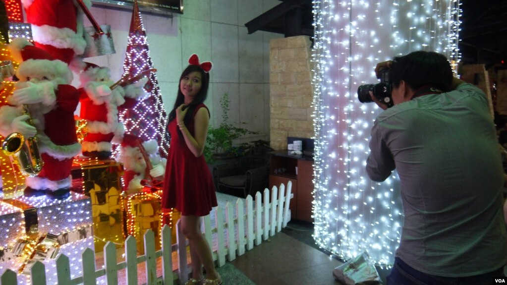 shoppers take photos in front of christmas decorations at a mall in ho chi minh city - Is Christmas A Religious Holiday