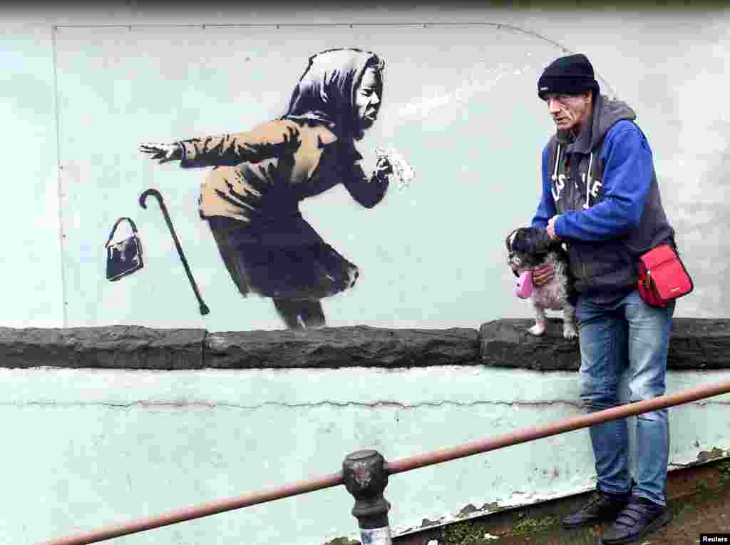 "A man stands near a new street artwork entitled ""Aachoo!!"" by Banksy in Totterdown, Bristol, Britain."