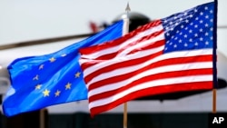 FILE - The U.S. and European Union flags wave at Dulles International Airport, Virginia, May 18, 2012.