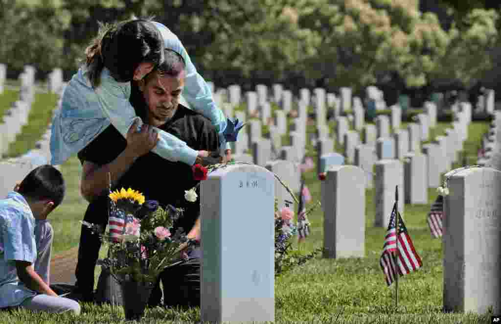 Carla Martinez comforts her cousin Ceaser Martinez as he weeps over his brother's grave on Memorial Day at the Veterans National Cemetery in Los Angeles. Rodrigo Matinez was killed in action in Iraq in 2004.