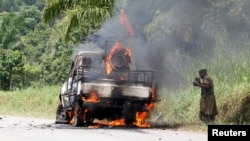 A Congolese soldier from the Armed Forces of the Democratic Republic of Congo stands next to their burning vehicle after an ambush near the village of Mazizi in North Kivu province, Jan. 2, 2014.