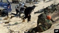 Libyan rebel fighters take cover during a shelling along Benghazi -Ajdabiyah road near Ajdabiyah March 24, 2011.