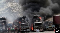 FILE - Smoke rises from NATO supply trucks following an attack by militants in Torkham, Afghanistan, Sept 2, 2013.