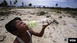 Seorang anak yang selamat dari tsunami sedang minum air dalam kemasan di daerah yang terkena tsunami.