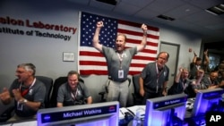 From left to right, Geoffrey Yoder, Michael Watkins, Rick Nybakken, Richard Cook and Jan Chodas celebrate in Mission Control at NASA's Jet Propulsion Laboratory as the solar-powered Juno spacecraft goes into orbit around Jupiter on Monday, July 4, 2016.