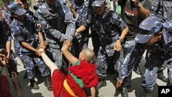 Nepalese police officers try to detain a Tibetan nun during a demonstration outside Chinese Embassy in Katmandu, Nepal, Wednesday, April 16, 2008.
