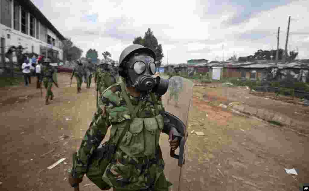 Un policier kenyan portant un masque à gaz dans le bidonville de Kibera, à Nairobi, au Kenya, 23 mai 2016.