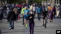 图为人们正在穿越西班牙马德里的托莱多大桥,周六,西班牙人能够外出锻炼,这是自封锁开始抗争以来的七周来的第一次。(2020年5月3日)