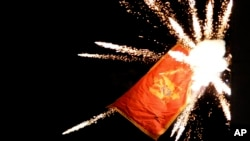 The Montenegrin flag flying from the Montenegrin Embassy, is targeted with fireworks by Serbian ultra-nationalists during a protest against a religion rights law adopted by Montenegro's parliament last month, during a mass protest in Belgrade, Serbia, Jan