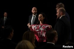 """A protester holding a sign that says """"Peace with Iran"""" is escorted out of the room during U.S. Secretary of State Mike Pompeo's remarks during the United Against Nuclear Iran Summit on the sidelines of the U.N. General Assembly in New York, Sept. 25, 2018."""