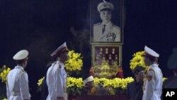 Vo Dien Bien (nomor dua dari kanan, berpakaian hitam), anak laki-laki Jenderal Vo Nguyen Giap dan pasukan kehormatan berdiri di dekat peti jenazah Giap di Tempat Persemayaman Nasional di Hanoi, Vietnam (12/10).