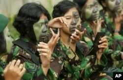Tentara perempuan sedang memakai kamuflase untuk bersiap mengikuti parade peringatan Hari TNI ke58 di Jakarta, 22 Desember 2003
