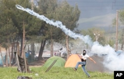 A migrant man throws a can of the tear gas back toward Macedonian police during a protest at the northern Greek border point of Idomeni, Greece, April 10, 2016.